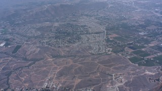 WA007_039 - 4K stock footage aerial video tilt from homes and fly over hills toward suburban neighborhoods, Riverside, California
