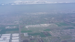 WA007_044 - 4K stock footage aerial video tilt from construction areas to reveal Chino Airport and snowy mountains, Chino, California