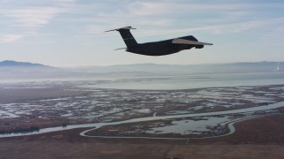 WAAF01_C004_0117UU - 4K stock footage aerial video of a Lockheed C-5 flying over marshland in Northern California
