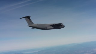 WAAF01_C012_0117G5 - 4K stock footage aerial video tilt to reveal a Lockheed C-5 flying over hills in Northern California