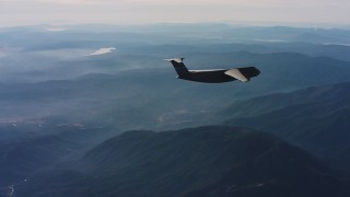 WAAF01_C027_0117SH - 4K stock footage aerial video of a Lockheed C-5 flying over mountains in Northern California