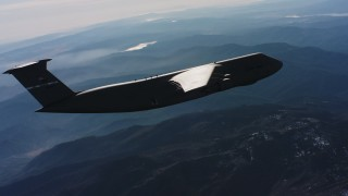 WAAF01_C029_01174N - 4K stock footage aerial video of a Lockheed C-5 flying high over mountains in Northern California