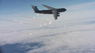 WAAF01_C048_0117DF - 4K stock footage aerial video of a Lockheed C-5 firing flares over clouds in Northern California