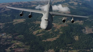 WAAF01_C069_0117TJ - 4K stock footage aerial video tilt from hills to reveal a Lockheed C-5 in Northern California