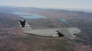 WAAF01_C074_0117TM - 4K stock footage aerial video of a Lockheed C-5 flying over mountains near a lake, Northern California