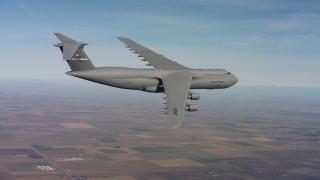 WAAF01_C078_0117MA - 4K stock footage aerial video of a Lockheed C-5 in flight over farmland in Northern California