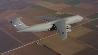 WAAF01_C079_0117FV - 4K stock footage aerial video of a Lockheed C-5 in flight over farm fields in Northern California