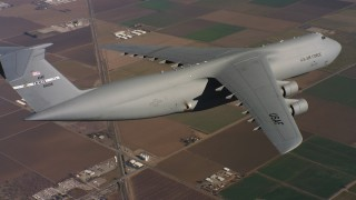 WAAF01_C081_0117PS - 4K stock footage aerial video of a Lockheed C-5 in flight over farms and leaving frame in Northern California