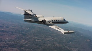 WAAF02_C004_0117QQ - 4K stock footage aerial video of a Learjet C-21 in flight over hills of Northern California