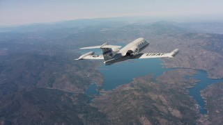 WAAF02_C007_0117AS - 4K stock footage aerial video of revealing a Learjet C-21 flying toward hills and a lake in Northern California