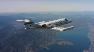 WAAF02_C008_0117ED - 4K stock footage aerial video reveal a Learjet C-21 flying over hills toward a lake in Northern California
