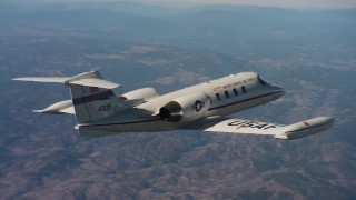 WAAF02_C009_01170N - 4K stock footage aerial video of flying around the tail of a Learjet C-21 over Northern California