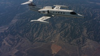 WAAF02_C013_01176E - 4K stock footage aerial video of a Learjet C-21 as it leaves frame, Northern California
