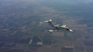 WAAF02_C014_0117MN - 4K stock footage aerial video of a Learjet C-21 as it turns and flies over farmland in Northern California