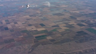 WAAF02_C016_0117AV - 4K stock footage aerial video of a reverse view of a Learjet C-21 over farmland in Northern California