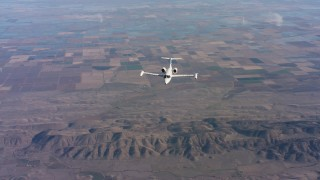 WAAF02_C017_0117TS - 4K stock footage aerial video of reverse view of a Learjet C-21 flying over farm fields in Northern California