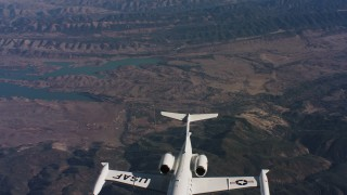 WAAF02_C018_0117VQ - 4K stock footage aerial video revealing a Learjet C-21 rising into frame over hills and a lake in Northern California