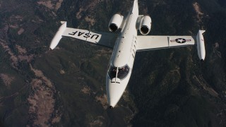 WAAF02_C019_0117JN_S001 - 4K stock footage aerial video of a Learjet C-21 flying in and out of frame over mountains in Northern California