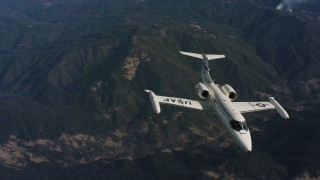 WAAF02_C020_0117TR - 4K aerial stock footage video of tracking a Learjet C-21 in flight over mountains in Northern California
