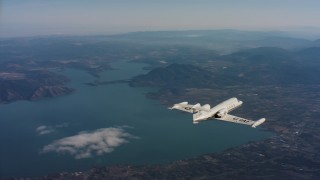 WAAF02_C021_0117PA - 4K stock footage aerial video fly around tail of a Learjet C-21 in flight near lake in Northern California