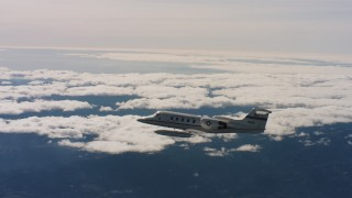 WAAF02_C022_01171S - 4K stock footage aerial video of a Learjet C-21 in flight near cloud-topped mountains in Northern California