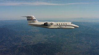 WAAF02_C028_0117BJ - 4K stock footage aerial video of a Learjet C-21 plane flying over mountains in Northern California