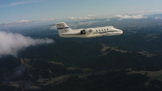 WAAF02_C031_01177D - 4K stock footage aerial video of a Learjet C-21 in the air over mountains in Northern California