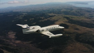 WAAF02_C032_0117R3 - 4K stock footage aerial video of a Learjet C-21 flying above mountains in Northern California