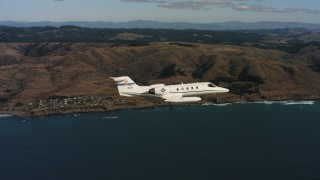 WAAF02_C034_0117KG - 4K stock footage aerial video of a Learjet C-21 flying over the ocean near the coast in Northern California