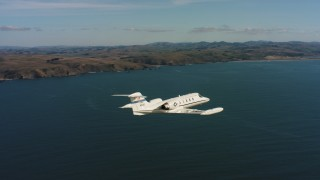 WAAF02_C036_0117TJ - 4K stock footage aerial video track a Learjet C-21 flying over the ocean near the coast in Northern California