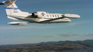WAAF02_C037_011796 - 4K stock footage aerial video of following a Learjet C-21 flying along the coast in Northern California