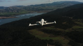 WAAF02_C040_0117KA - 4K stock footage aerial video reveal a Learjet C-21 while flying over hills on the coast in Northern California