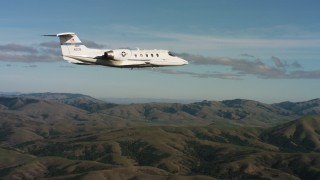 WAAF02_C042_0117T2 - 4K stock footage aerial video of a Learjet C-21 flying near hills in Northern California