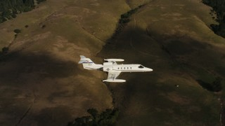 WAAF02_C045_011782 - 4K stock footage aerial video of panning across hills to reveal a Learjet C-21 in flight in Northern California
