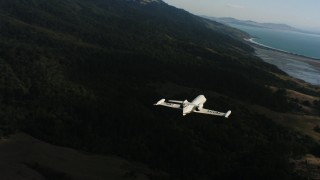 WAAF02_C047_0117D7 - 4K stock footage aerial video of a Learjet C-21 flying over coastal hills in Northern California