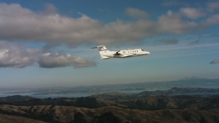 WAAF02_C050_0117QE - 4K aerial stock footage video of a Learjet C-21 over the Marin Hills, California