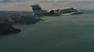 WAAF02_C054_0117PF - 4K stock footage aerial video of a Learjet C-21 flying over the bay, Northern California