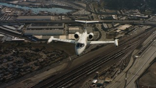 WAAF02_C054_0117PF_S001 - 4K stock footage aerial video of a reverse view of a Learjet C-21 flying over industrial and residential areas in Northern California