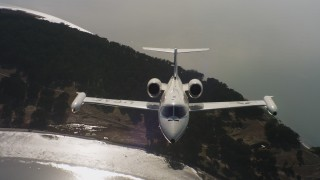 WAAF02_C056_011763 - 4K stock footage aerial video a reverse view of a Learjet C-21 flying over a bay in Northern California