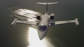 WAAF02_C058_0117FF - 4K stock footage aerial video tilt from sunlight reflecting on water to a Learjet C-21 in Northern California