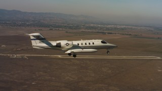 WAAF02_C065_0117R0 - 4K stock footage aerial video of a Learjet C-21 flying near Travis Air Force Base, California