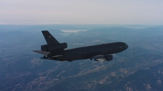 WAAF03_C012_0118D4 - 4K stock footage aerial video of revealing a McDonnell Douglas KC-10 flying over hills in Northern California