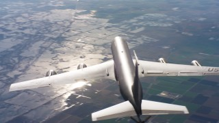 WAAF04_C020_011886 - 4K stock footage aerial video of flying around the tail of a Boeing KC-135 in flight over Northern California mountains