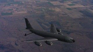 WAAF04_C022_0118CS - 4K stock footage aerial video of a Boeing KC-135 flying over farms with lowered fuel boom in Northern California