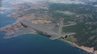WAAF04_C069_011863 - 4K stock footage aerial video of revealing a Boeing KC-135 as it flies over coastal clouds in Northern California