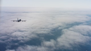 WAAF04_C069_011863_S000 - 4K aerial stock footage video of a Boeing KC-135 flying over low coastal clouds in Northern California