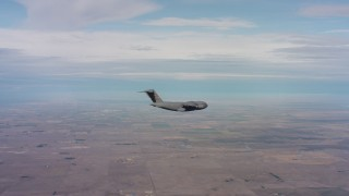 WAAF05_C006_0118HE - 4K stock footage aerial video of a Boeing C-17 flying over farmland in Northern California