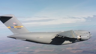 WAAF05_C010_0118DP - 4K stock footage aerial video of a Boeing C-17 in flight over farmland, Northern California