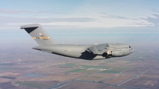 WAAF05_C011_01185N - 4K stock footage aerial video of a Boeing C-17 flying over farm fields in Northern California