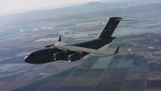 WAAF05_C013_01184S - 4K stock footage aerial video of a Boeing C-17 in flight over wetlands, Northern California